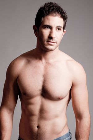 male muscles muscular pecs pectoral sexy young: Fit man showing chest and abs on a grey background Stock Photo