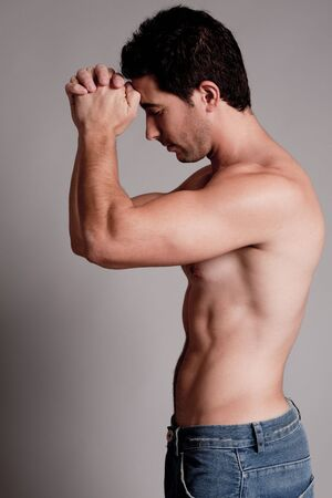 male muscles muscular pecs pectoral sexy young: Shirtless man hold his hands on the head on a grey isolated background