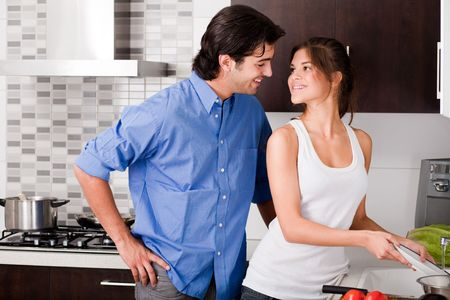 smiling young couple enjoying their love in kitchen photo