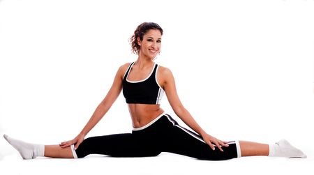 both sides: Fitness girl sitting and streching  her legs both sides on white background Stock Photo