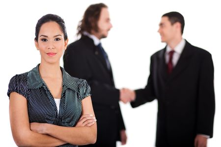 Smiling business women in focus with two business collegue welcoming each other behind her out of focus photo