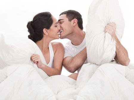 enamorados en la cama: Pareja bes�ndose y jugando en cama en el dormitorio, en pasi�n sobre fondo blanco