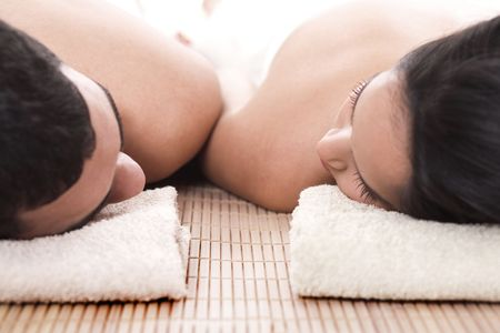 couples therapy: Young man and woman lying on towel to take spa in isolated background