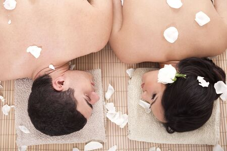 Portrait of fresh and beautiful man and woman lying around flowers and taking spa treatment over white background photo