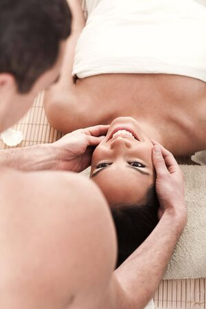 Man giving head massage to his girl friend over white background photo