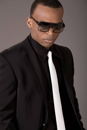 black business man: Serious black business man with sunglasses on grey background