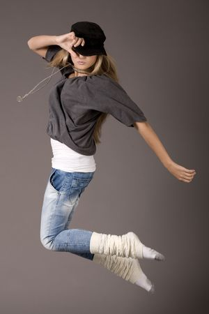 Young women jumping during her dance on grey background photo