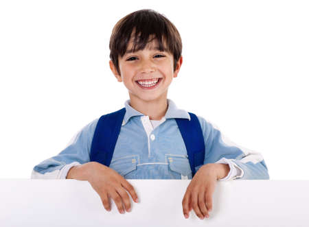 Smiling young boy behind the blank board on isolated white background photo