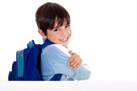 Young school boy showing hins fingers down from behind the board on white background photo
