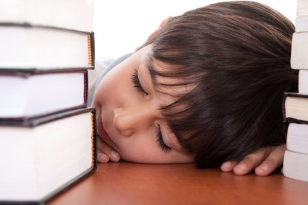 School boy tired of studying and sleeping with books on isolated background Stock Photo