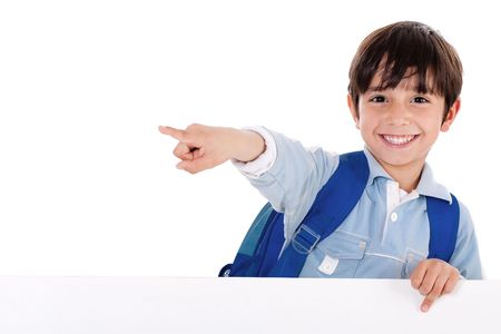 Smiling young boy standing behind the blank board and pointing us on isolated white background