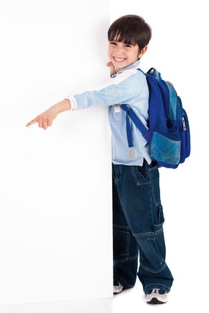 Young kid happily standing behind the board and pointing to empty space on white isolated background photo