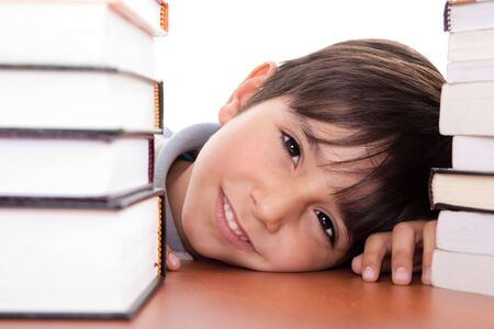 Happy young school boy surrounded by books on white background photo