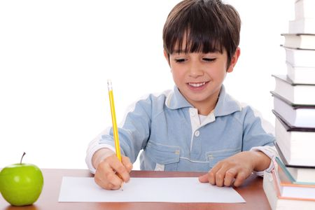 School boy doing his homework with an apple beside him on white background photo
