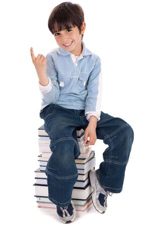 Young boy sitting over tower of books on white background photo
