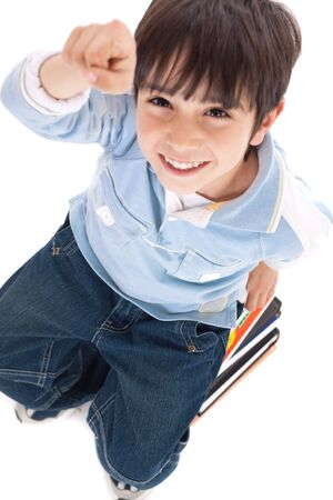 Top view of cute kid with fingers up sitting on books over white background photo