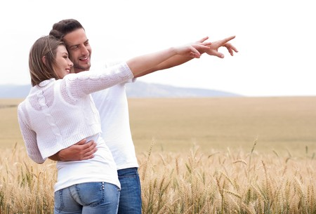 Young couple in meadow pointing in the air, hugging in the park photo