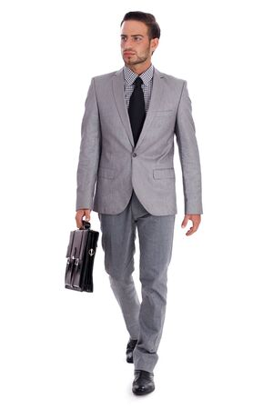 briefcase: Businessman carrying briefcase and walking on isolated white background..