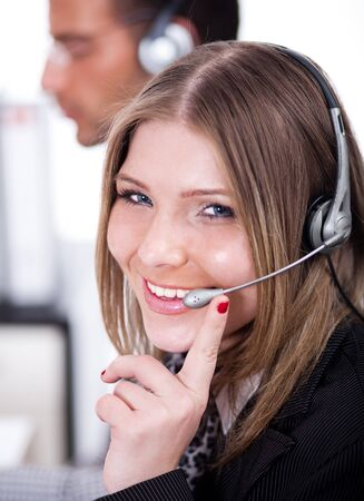 customercare: smiling business woman speaking through head phone with the customer in her cabin