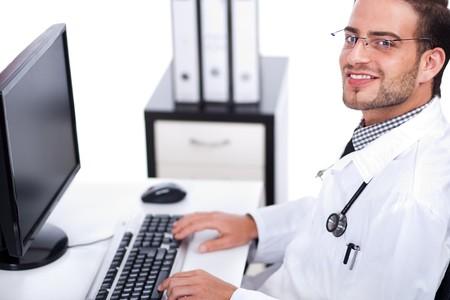medico computer: Sorridente giovane medico lavorando sulla sua scrivania su uno sfondo bianco  Archivio Fotografico