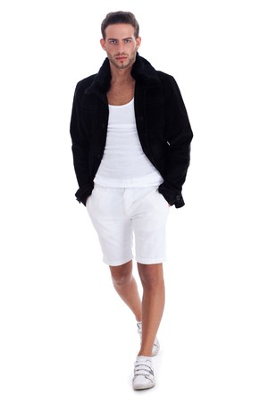 casual wear: Handsome  guy in casual wear walking by putting his hands in pockets over white background