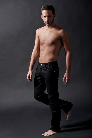Fashion male model with black jean over black background photo