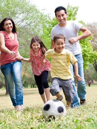 Happy family run to the soccer ball in the park, outdoor Stock Photo - 6956488