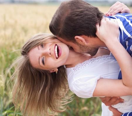 pareja abrazada: Close up of un Happy joven pareja bes�ndose en el Parque Foto de archivo
