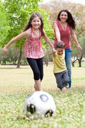 futbol infantil: Para los niños jugando al fútbol con su madre en el Parque