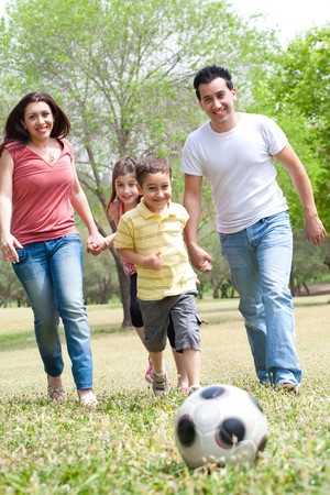 Family outdoor playing soccer and having fun photo
