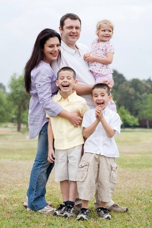 Happy family posing together with smile in the park on natural background photo