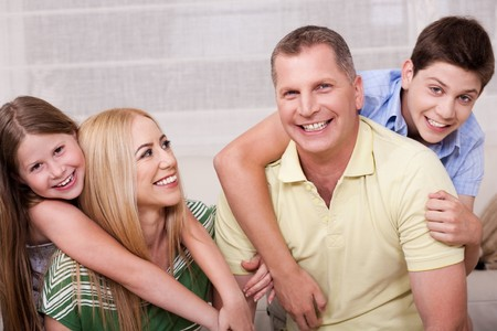 Portrait of lovely family having fun together in living room and looking at you Stock Photo - 7169128