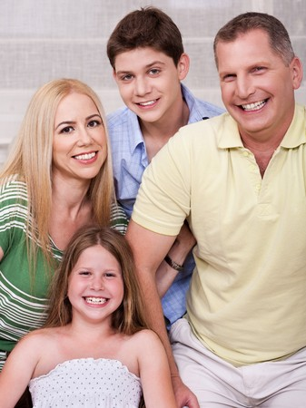 Portrait of happy familyof four posing and looking at you photo