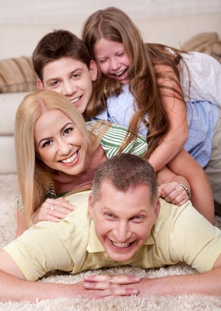 Portrait of happy family Lying On Top Of Each Other In living room photo