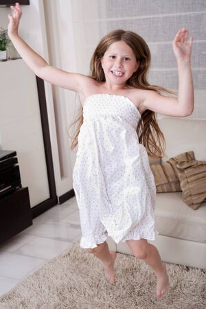Young little girl jumping with joy in living room Stock Photo - 7169090