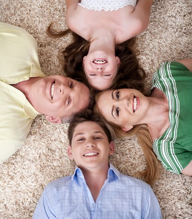 Portrait of happy family lying on carpet with their heads close together and smiling. photo
