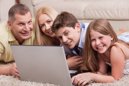 Domestic family of four lying in living room with lap top and looking at you Stock Photo - 7169104