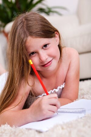 Smiling young girl with pencil and notebook in living room looking at you Stock Photo - 7169116