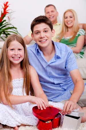 Happy young kids with gift boxes in living room and the parents in the background photo