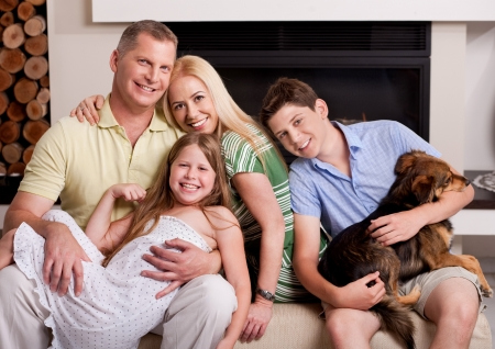 Happy domestic family sitting in living room with dog and looking at you photo