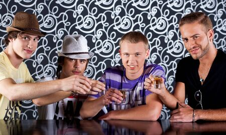 Four attractive people drinking in cocktail party at disco club Stock Photo - 7169568