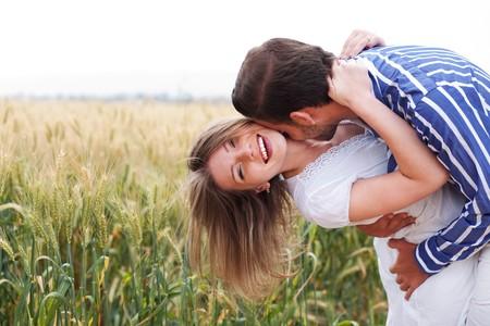 personas abrazadas: Feliz pareja joven abrazos y besos de eachother, al aire libre Foto de archivo