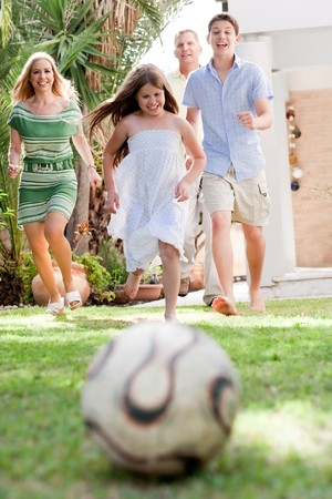 Happy family playing soccer and running towards the camera in the backyard of their home photo