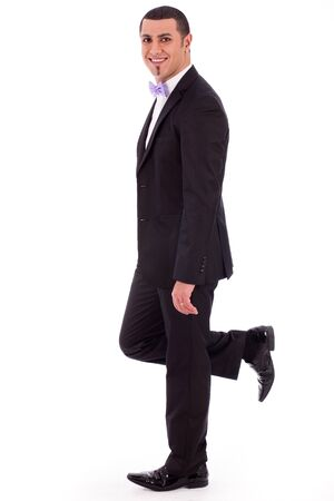Full length of a business man leaning against the wall on a white isolated background photo