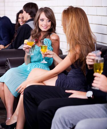 lady's: Two ladys at party talk each other and drink cocktail
