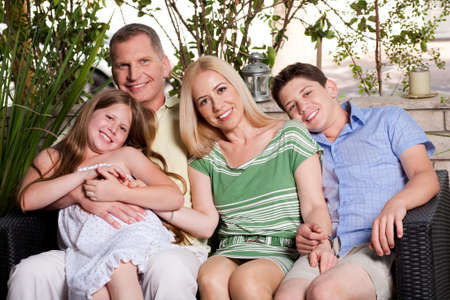 happy family sitting in patio and looking at you and smiling photo