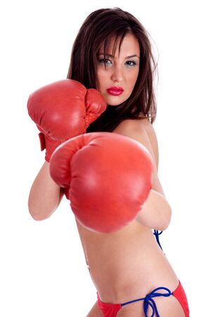 Young Woman in red bikini doing boxing excercise with red gloves, indoor studio over white background photo