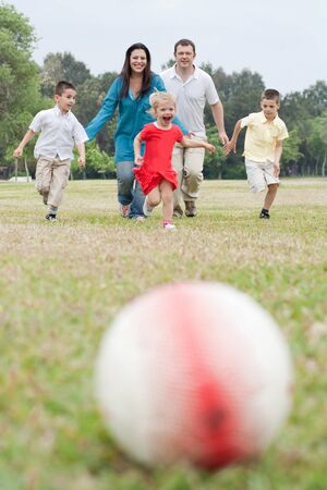 Happy family of five having outdoors and playing soccer running towards the football on natural background photo