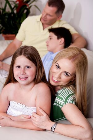 Mom and daughter in focus facing camera with father and boy in the background, all relaxing on couch Stock Photo - 7368609
