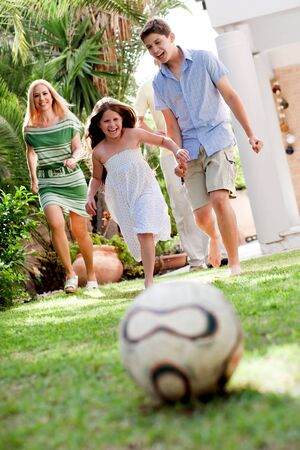 Cute girl rushing towards football as her brother and mom follow her photo
